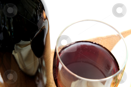 Glass Of Red Wine stock photo, A single glass of red wine viewed from above with the surrounding scenery reflected in the bottle on a light colored background. by Lynn Bendickson