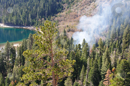 Fire And Smoke In The Forest stock photo, Dense smoke rising from the pine forest where a fire has started surrounded by steep hillsides and an emerald green colored lake by Lynn Bendickson