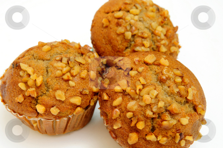 Banana Muffin With Waluts stock photo, Three banana nut muffins topped with crushed walnuts on a light colored background. by Lynn Bendickson