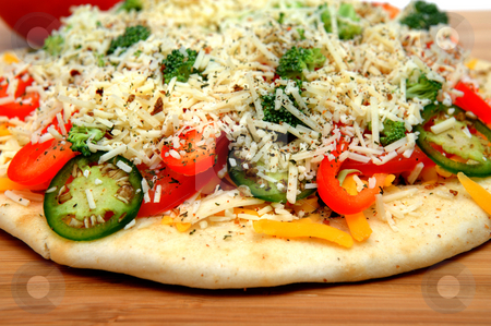 Uncooked Vegtable Pizza For One stock photo, A veggie pizza ready to go into the oven topped with sharp cheddar and asiago cheese, fresh tomatoes, red bell pepper, mild jalapeno chilie, broccoli and dried herbs by Lynn Bendickson