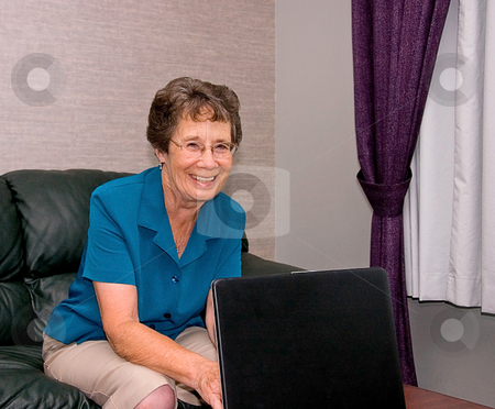 Elderly Woman on Laptop Computer stock photo, This elderly senior woman is smiling while working and learning on her laptop computer. by Valerie Garner