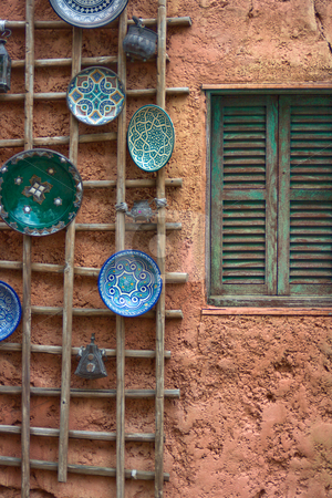 Plates on a Wall stock photo, Painted blue and green plates hanging on a wodden frame attached to a exterior wall with a window that has wooden shutters on it by Keith Wilson