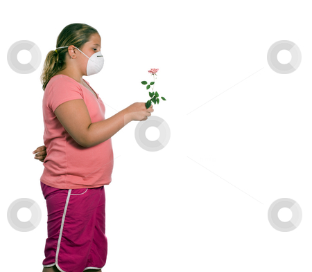 Allergy stock photo, A young girl holding a flower while she wears a mask, isolated against a white background by Richard Nelson