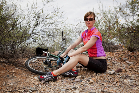 Woman with Mountain Bike stock photo, Young woman sitting next to mountain bike by Scott Griessel