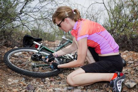 Woman Repairing Mountain Bike stock photo, Young woman sitting next to and repairing mountain bike by Scott Griessel