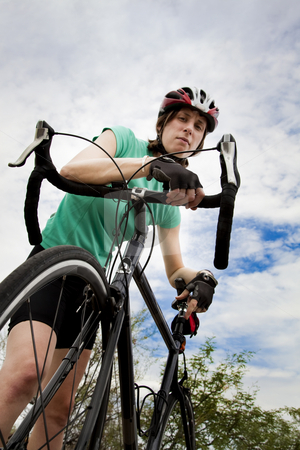 Woman with Bicycle stock photo, Young woman wearing helmet leaning on a bicycle by Scott Griessel