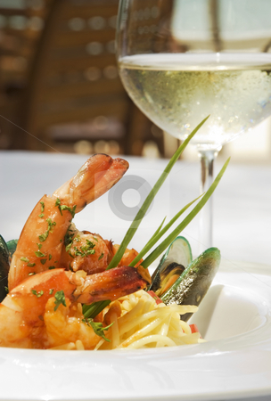 Shrimp and oyster spaghetti stock photo, Shrimp and oyster spaghetti served in a white ceramic plate and accompanied with a glass of a white wine. by Stefan Breton