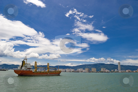 Cargo Ship stock photo, A large red cargo shipping vessel going through a strait and into the port of Penang in Malaysia. by Stefan Breton