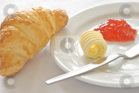 Croissant with butter and jam stock photo, An image of a freshly baked croissant served on white ceramic plate with a portion of butter and jam. by Stefan Breton