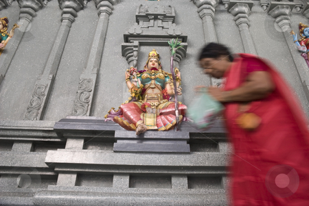 Worshipping Lakshmi stock photo, An old Indian woman worshipping the colorful stone wall statue of the Hindu deity Lakshmi, Goddess of wealth, prosperity, light, wisdom, fortune, fertility, generosity and courage; and the embodiment of beauty, grace and charm. by Stefan Breton