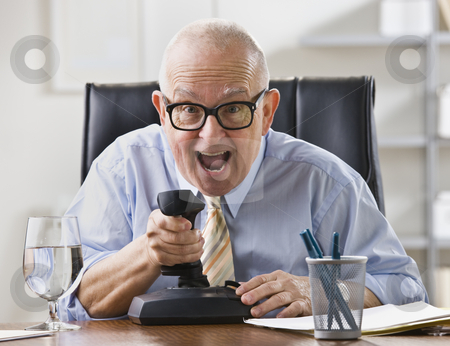 Man in Office stock photo, An elderly businessman is seated at a desk in his office and is joking around.  He is looking at a camera.  Horizontally framed shot. by Jonathan Ross