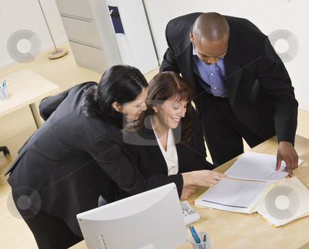 Man and Women Working in Office stock photo, A group of business people are working together in an office. They are looking at paperwork.  Horizontally framed shot. by Jonathan Ross