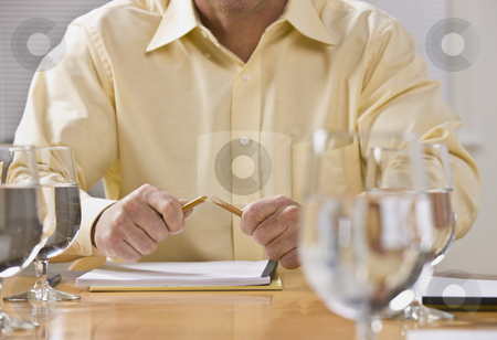 Man Breaking Pencil stock photo, A man is seated at a table with a broken pencil in his hands.  Horizontally framed shot. by Jonathan Ross