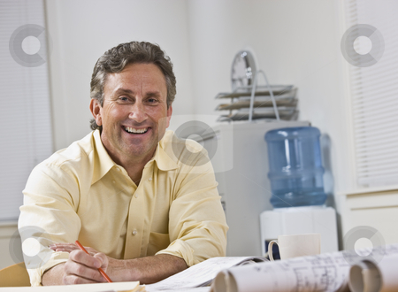 Man Smiling at Camera stock photo, A businessman is seated at a desk in an office.  He is smiling at the camera.  Horizontally framed shot. by Jonathan Ross
