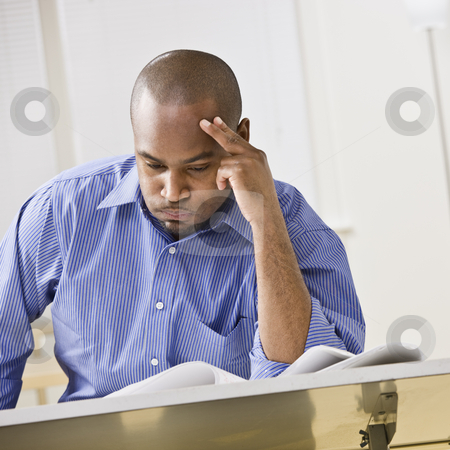 African-American Man Studying stock photo, An attractive African-American male studying at a desk. He is resting his head against his fingers, and is puffing his cheeks out with air.  Square composition. by Jonathan Ross