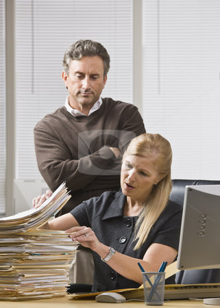 Man Looking Over Woman's Shoulder stock photo, A businessman is standing in an office and looking over a woman's shoulder at the files on her desk.  She is looking away from the camera. by Jonathan Ross