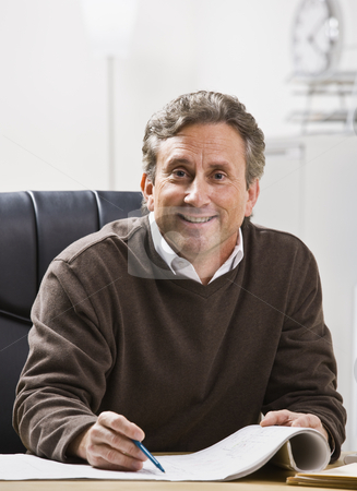Man in Office stock photo, A businessman is seated at a desk in an office and is smiling at the camera.  Vertically framed shot. by Jonathan Ross