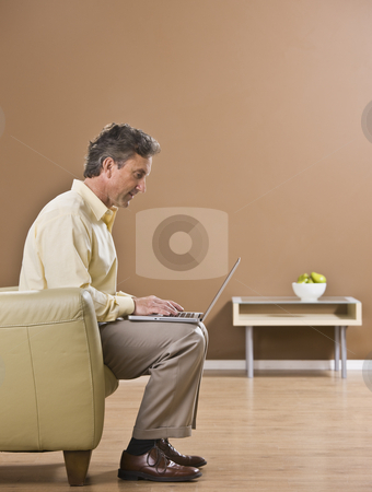 Attractive Business Man Using Laptop stock photo, The side view of an attractive business man using a laptop.  He is seated on a sofa.  Vertically framed shot. by Jonathan Ross