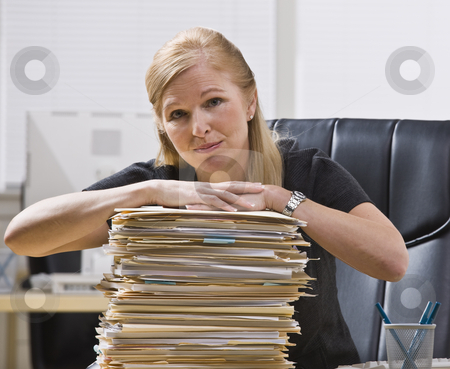 Woman with Paperwork stock photo, A businesswoman is seated at a desk with a large stack of paperwork in front of her.  She is looking at the camera.  Horizontally framed shot. by Jonathan Ross