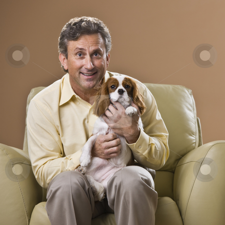 Man with Puppy stock photo, A man is seated in a chair holding a puppy.  He is smiling at the camera.  Square framed shot. by Jonathan Ross