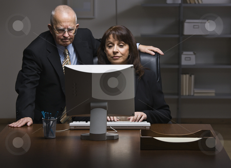 Man and Woman Working on Computer stock photo, An elderly businessman and businesswoman are working together on a computer.  They are looking away from the camera.  Horizontally framed shot. by Jonathan Ross