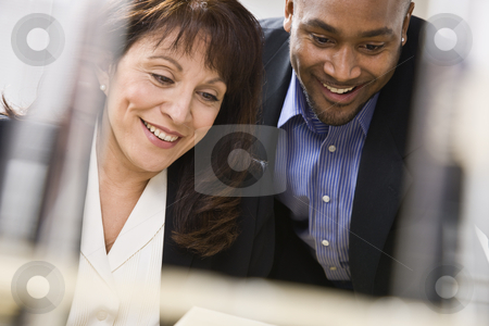 Man and Woman Working in Office stock photo, A businessman and woman are working together in an office.  They are smiling and looking away from the camera.  Horizontally framed shot. by Jonathan Ross