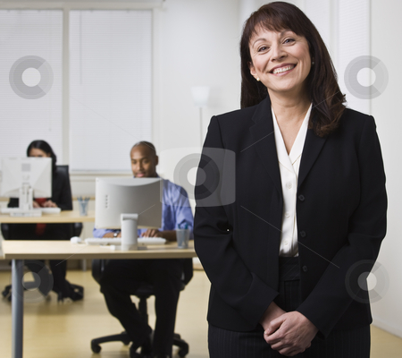 Woman in Office with Co-workers stock photo, A businesswoman is standing in an office while her coworkers are seated at computer desks.  She is smiling at the camera.  Horizontally framed shot. by Jonathan Ross