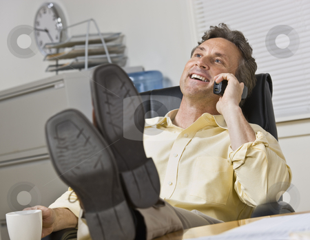 Attractive business man on phone. stock photo, Attractive business man leaning back in chair, with legs on desk while chatting on the phone. Horizontal. by Jonathan Ross