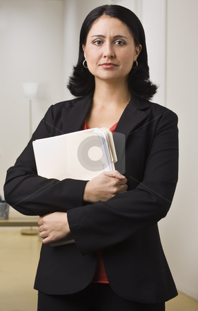 Woman in Office stock photo, A businesswoman is standing in an office holding some paperwork.  She is looking at the camera.  Vertically framed shot. by Jonathan Ross