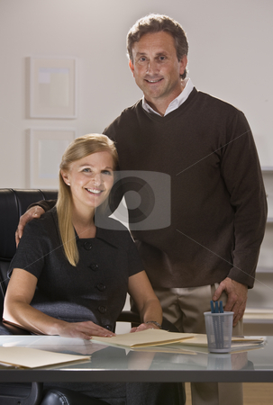 Attractive couple at office. stock photo, Attractive couple at office with man standing over woman sitting at desk, looking at camera. Vertical. by Jonathan Ross
