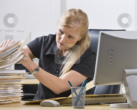 Woman Looking Through Paperwork stock photo, A businesswoman is seated at a desk in an office and is looking through a stack of paperwork.  Horizontally framed shot. by Jonathan Ross