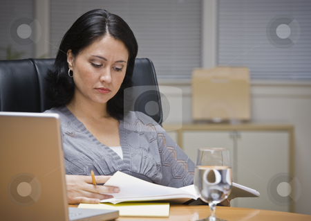 Woman Working in Office stock photo, A young businesswoman is seated at a desk in an office.  She is looking away from the camera.  Horizontally framed shot. by Jonathan Ross