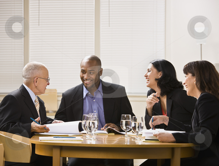 Businesspeople in Meeting stock photo, A group of business people are in a meeting in an office.  They are talking and laughing and looking away from the camera.  Horizontally framed shot. by Jonathan Ross
