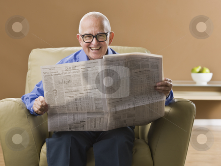 Elderly Man Reading Newspaper stock photo, An elderly man is sitting in his living room reading a newspaper.  He is smiling at the camera.  Horizontally framed shot. by Jonathan Ross