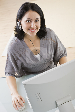 Woman on Computer stock photo, A young businesswoman is seated in front of a computer and is smiling at the camera.  Vertically framed shot. by Jonathan Ross