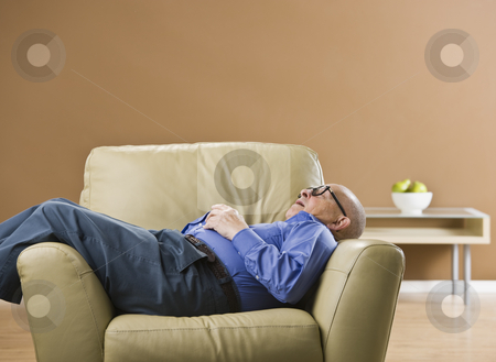 Senior man sleeping on chair. stock photo, Senior man sleeping on chair with glasses on and hands folded on chest. Horizontal by Jonathan Ross