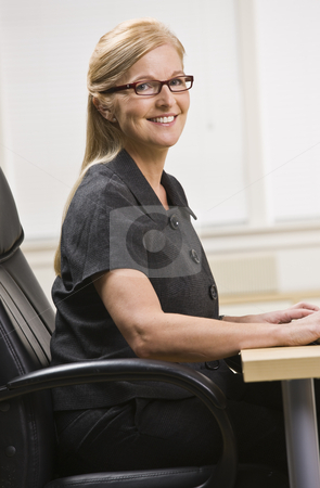 Woman at Desk stock photo, An older woman is seated at a desk in an office and is smiling at the camera.  Vertically framed shot. by Jonathan Ross