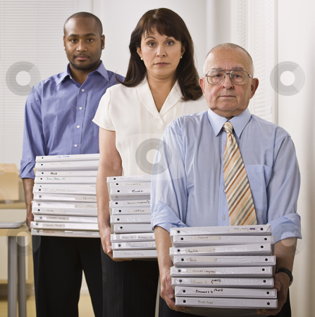 Business People Holding Binders stock photo, Three Business People are standing in an office, holding binders, and looking at the camera.  Square framed shot. by Jonathan Ross