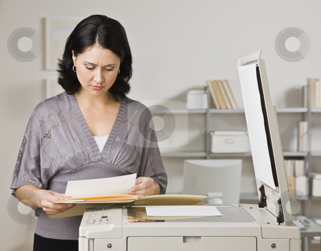 Woman Making Copies stock photo, A businesswoman is making copies in an office.  She is looking away from the camera.  Horizontally framed shot. by Jonathan Ross