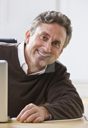 Man Smiling at Camera stock photo, An older man is sitting at a desk and smiling at the camera.  Vertically framed shot. by Jonathan Ross