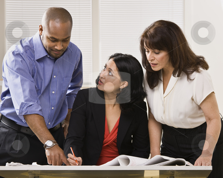 Women and Man Working in Office stock photo, A group of business people are in an office and are looking at some paperwork.  They are talking and looking away from the camera.  Horizontally framed shot. by Jonathan Ross