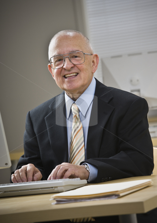 Attractive senior male smiling at camera stock photo, Attractive senior male smiling at camera, working on keyboard at desk. Vertical by Jonathan Ross