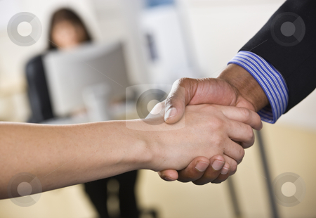 Man and Woman Shaking Hands stock photo, A businessman and woman are shaking hands in an office.  Horizontally framed shot. by Jonathan Ross