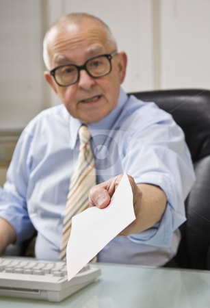 Man Holding out Paper stock photo, An elderly businessman is holding out a piece of paper in front of him.  He is looking at the camera.  Vertically framed shot. by Jonathan Ross