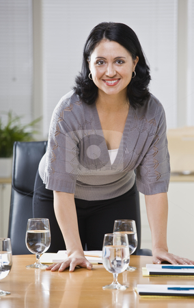 Woman in Office stock photo, A young businesswoman is standing over a desk in an office and is smiling at the camera.  Vertically framed shot. by Jonathan Ross