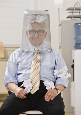 Man with Wastebasket on Head stock photo, An elderly man is seated in an office with a wastebasket on his head.  He is looking at the camera.  Vertically framed shot. by Jonathan Ross
