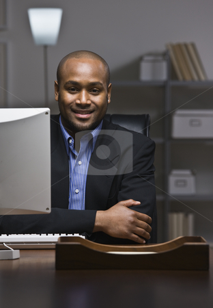 Business man smiling. stock photo, African American business man smiling at camera, sitting at desk with computer monitor. Vertical by Jonathan Ross