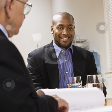 Men in Meeting at Office stock photo, Two businessmen are in a meeting at an office.  The younger man is smiling at the camera.  Square framed shot. by Jonathan Ross