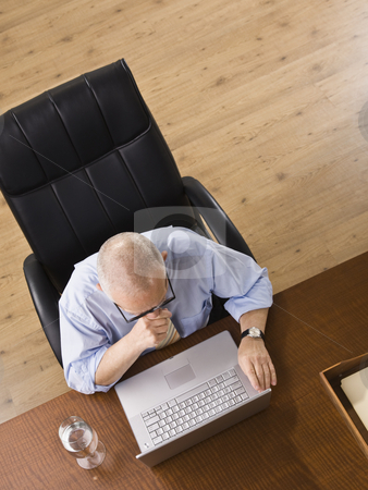 Elderly man on Laptop stock photo, An elderly man is seated at a desk and is working on a laptop.  He is looking away from the camera.  Horizontally framed shot. by Jonathan Ross