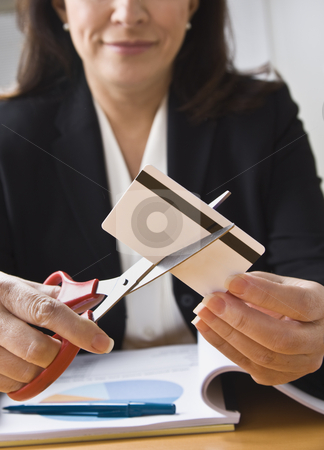 Woman Cutting Credit Card stock photo, A businesswoman is cutting up a credit card with a pair of scissors.  Vertically framed shot. by Jonathan Ross